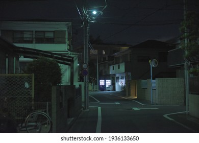 Zone urbaine résidentielle dans la banlieue de Tokyo, vue sur une rue vide éclairée par la couleur verte des lampadaires LED avec des distributeurs de boissons en arrière-plan