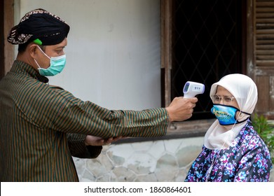 Residents in traditional Javanese Lurik and Batik clothing carry out health protocols using masks and body temperature tests to prevent the spread of Covid19 in Yogyakarta, 12 September 2020