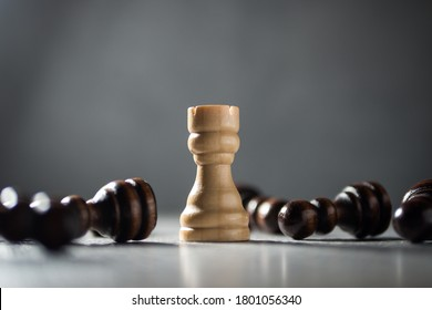 Resilience, perseverance, immunity and victory concept. Rook standing among fallen pawns.
