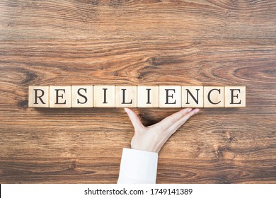 Resilience word on wooden building blocks with supporting hand. Recovering and building resilience concept, coping with crisis. Copy space - Shutterstock ID 1749141389