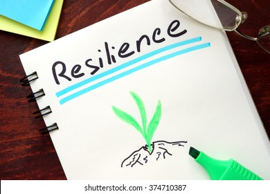 Resilience written on notepad on a table.