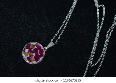 Resin necklace with dry rose petals on a dark background close up