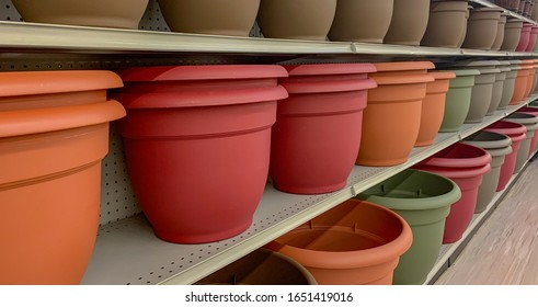 Resin/plastic pot planters on a display shelf at a gardening department.