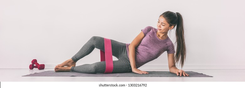 Resistance band clamshell exercise fit girl training legs on floor mat demonstration. Hip abductor workout for burning calories.