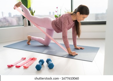 Resistance band fitness at home Asian woman doing leg workout donkey kick floor exercises with strap elastic. Glute muscle activation with kickback for thighs cellulite. - Shutterstock ID 1677610060