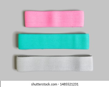 Resistance bands for exercise and physical therapy in three colors and sizes isolated on gray background