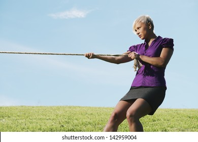 resolute business woman pulling rope against blue sky, symbol of power and determination. Copy space, side view