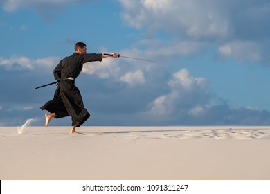Resolute man, in traditional clothes, is practicing Japanese martial art - iaido in the desert with a Japanese sword, katana, during sunset.