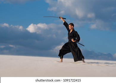 Resolute man, in traditional Japanese clothes with sword, katana, is training martial arts in desert during sunset - samurai on the cloudy sky background.