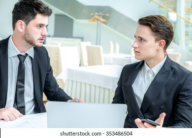 Resolution of the dispute. Two successful businessman sitting at the table and discussing business at the a laptop in a restaurant. Businessmen dressed in formal wear.