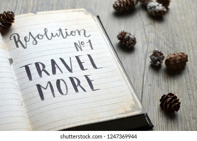 Resolution No. 1 TRAVEL MORE written in notepad with pine cones on wooden background