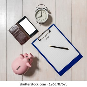 Resolutions for 2019 with piggy bank, alarm clock and smartphone