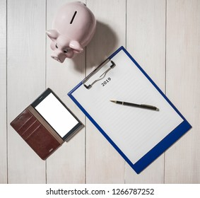 Resolutions for 2019 with piggy bank and smartphone, flat lay