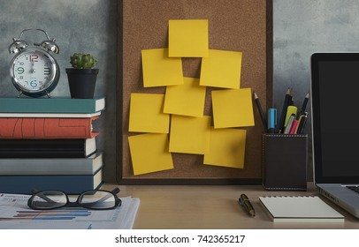 Resolutions, notes, goals, post, memo or action plan concept. Sticky notes on cork board in workplace office with laptop, notebook, eye glasses, clock, plant, books and stationery on wooden desk.