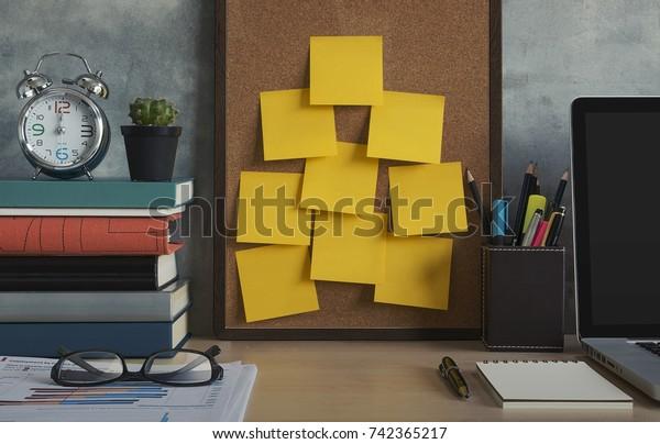 解決、メモ、目標、投稿、メモ、またはアクションプランのコンセプト。オフィスのコルク板に付いた付箋。ノートパソコン、ノートパソコン、眼鏡、時計、植物、本、文房具を木の机の上に置く。