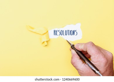 Resolutions word message written on ripped pieces of cardboard paper