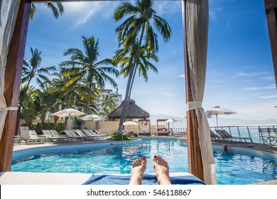 Resort Cabana with Woman's Feet by Pool View Perspective from Lying Down by Beach