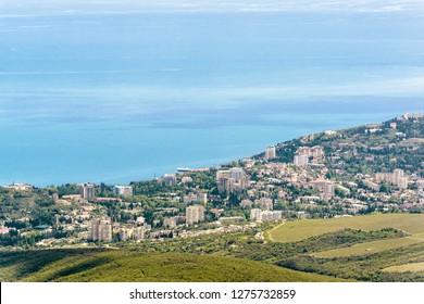 Resort city of Alushta from above, Crimea, Russia. Aerial panoramic view of Alushta. Landscape of Crimea with seaside town in summer. Scenic panorama of Black Sea coast. Scenery of Southern Crimea.