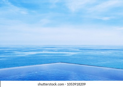 Resort style infinity edge pool with tropical blue sea and clear sky. Wide angle shot with copy space