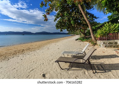 A resort with two empty chair are waiting on Phuket beach, Thailand.