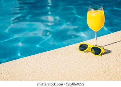 Resort vacation concept - close-up sunglasses and glass of juice on a bright sunny day by the pool - copy space