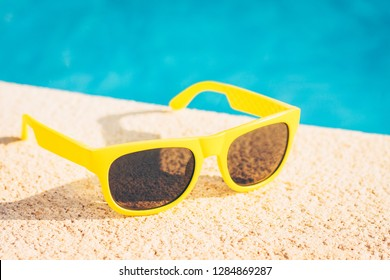 Resort vacation concept - close-up sunglasses on a bright sunny day by the pool - copy space