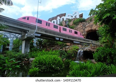 Resorts World Sentosa, Singapore - July 23, 2019: Portrait of pink monorail passed under Sentosa sign in Resorts World Sentosa Singapore.