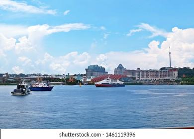 Resorts World Sentosa, Singapore - July 25, 2019: Portrait of ships with Resorts World Sentosa in background.