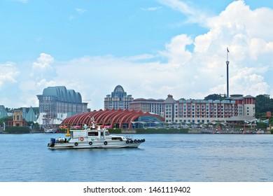 Resorts World Sentosa, Singapore - July 25, 2019: Portrait of a ship with Resorts World Sentosa in background.