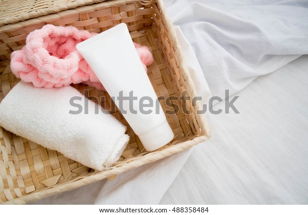 Resources for skincare products, white towel, headband, face wash tube, top view photography of tube in basket