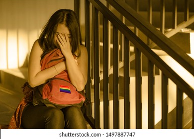 respect for homosexual and anti sexual discrimination campaign. Young beautiful depressed and scared Asian student woman with gay flag on her backpack victim of abuse and bullying
