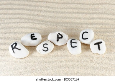 Respect word on group of stones with sand as background