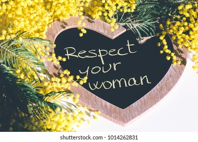 Respect your woman written on blackboard surrounded by mimosa flowers