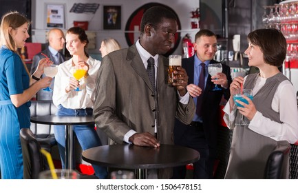 Respectable African man enjoying conversation with female colleague on corporate party in bar