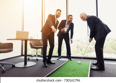 Respectable elderly man in a black business suit playing mini-golf in his office. Nearby are his assistants and watching