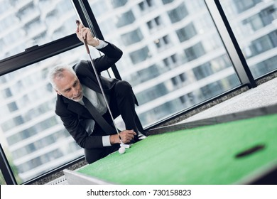 A respectable elderly man playing a mini golf in the office. He exposes the ball before the blow, standing on one knee and leaning on a golf club
