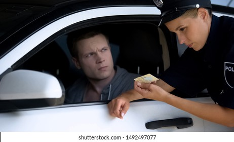 Respectable police woman checking driver license of man in car, road inspection
