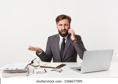Respectable worthy company manager sitting at desktop, has unpleasant telephone conversation, feels angry, he is told absurd ridiculous nonsensical things, dressed in a suit with a tie, has beard