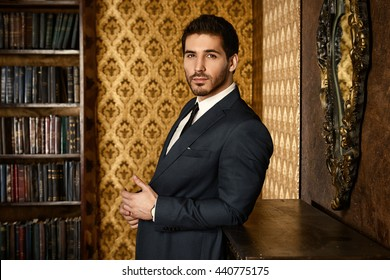 Respectable young man standing by a fireplace in a room with classic interior. Luxury. Men's beauty, fashion.