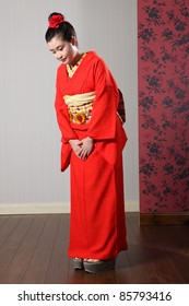 10bc138a1f Respectful bow by beautiful young oriental model in red Japanese kimono  robe garment complete with obi