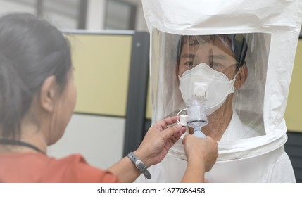 Respirator fit test prepared for COVID-19. Asia man testing repiratory system with N-95 surgical mask to checks properly fits face to wears.