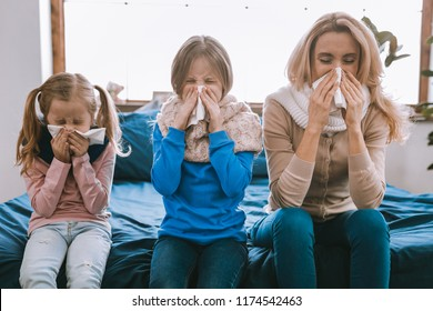 Respiratory disease. Unhappy cheerless family using paper tissues while sneezing