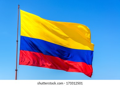 Resplendent Colombian flag waving in the wind set against a beautiful blue sky