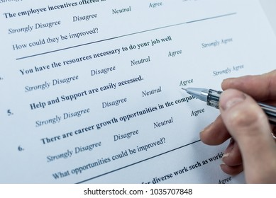 Respondent holding a pan in a hand and answeing questions in employee survey. Questions relating to managerial practices, corporate culture, career growth, and professional relationships.