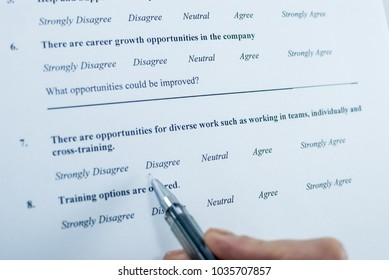 Respondent holding a pan in a hand and answeing questions in employee survey. Questions relating to managerial practices, corporate culture, career growth, and professional relationships. Close-up