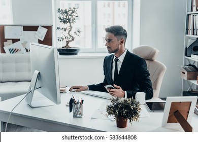 Responding on e-mail. Serious young man in formalwear holding smart phone and working using computer while sitting at the office desk