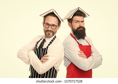 Responsibilities of household. Men bearded apron reading book about culinary. Men in charge household. Some problems. Household duties. Book as roof on head. Household is boring. Who rules in house.
