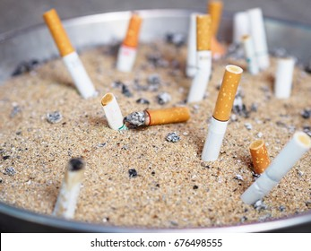 The rest of cigarettes in the ashtray. There are many types of cigarette stub on the sand in the ashtray. A cigarette is not good for health. It is not allow to smoking in the public area in Thailand.