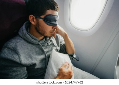 Rest and comfortable flight in the plane. man in a mask for sleeping, sits in the airplane's chair near the porthole.