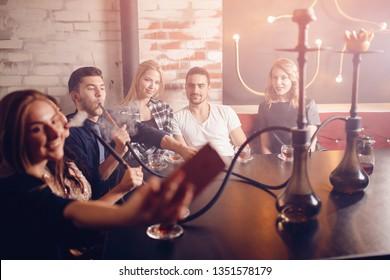 Rest hookah, nightlife of young people smoke shisha in nightclub and bar.